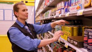 Butiksanställd sorterar energidrycker vid en hylla i S-market Hangö.