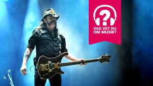 Lemmy Kilmister står med hatt på huvudet och en elbas hängande från halsen.