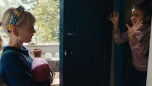 Ett barn tittar mot ett annat barn som tittar ut genom en dörr med händerna i luften