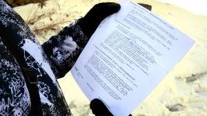 Person som läser ett papper.