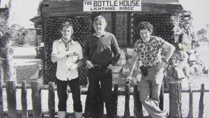 kolme miestä seisoo aidan vieressä, takana myymälä tai kapakka