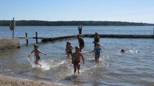 Simskolebarn som springer upp ur vattnet