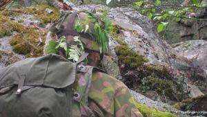 Militär i terrängen, axel i terrängkläder syns mot stenar och mossa.