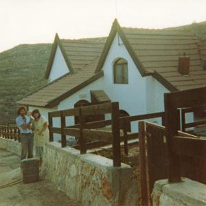 Mies, sylissään pieni poika ja nainen talon edessä Israelissa