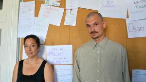 En kvinna och en man står framför en anslagstavla och tittar in i kameran.