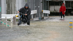 Människor i Japan rör sig på översvämmad gata.