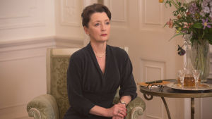Närbild på Cyril (Leslie Manville) som sitter på en stol och ser bestämd ut.