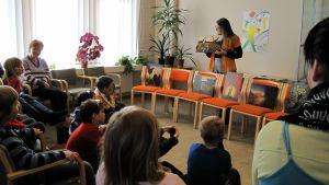 Eva Hietanen läser saga på biblioteket i Vörå.
