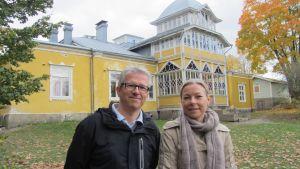 Mikaelskolans rektor Thomas Metzner och föräldraföreningens ordförande Birgitta Forsström framför den gamla skolbyggnaden i Västerby, Ekenäs.
