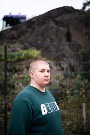 En allvarsam man står framför ett staket och en klippa. Han tittar in i kameran.