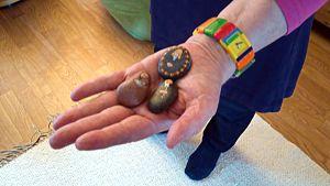 Isela håller i sin hand tre målade stenar - en amdonna, en nunna och en präst.
