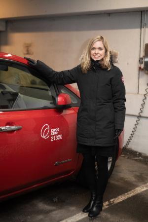 En kvinna står brevid en röd bil. Hon ser in i kameran. Bilen och kvinnan står i ett parkeringsgarage.