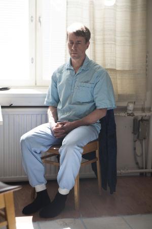 En man sitter på en stol framför ett fönster. Han ser ledsen och och har knäppt händerna.