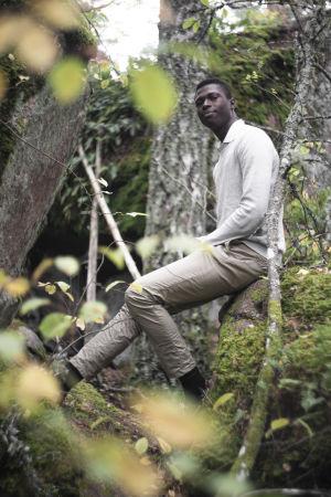 En man sitter på en sten i en skog. I bakgrunden syns löv och en björk.  Han ser in i kameran och ser nöjd ut.