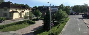 Tomma bussperronger, gator och ett gult gammalt trähus. Gräs och buskar, blå himmel, sommar.