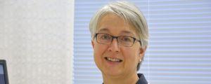Maria Silfverberg, en äldre kvinna med glasögon och kort grått hår står i en läkarrock på ett kontor.