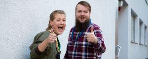 En ung kvinna och en ung man med scouthalsdukar runt halsen visar tummen upp och tittar in i kameran.