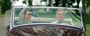 Märta och Roosevelt sitter i en bil sedd framifrån, båda ler.