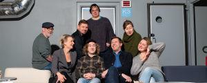 Radio Stagen ääninäyttelijät istuvat yhdessä sohvilla nauraen.