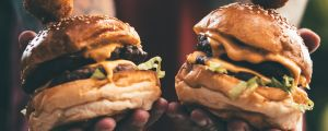 Kaksi mehevää hampurilaista ihmisen käsissä.