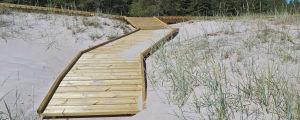 Ett promenadstråk i trä, byggt bland sanddynerna på en strand.