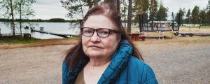 Yrittäjä Salme Uusitalo kuvattuna Valkeisen järven rannalla, taustalla leirintäalueen reunaa ja järvi.