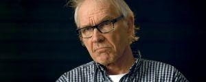 Lars Vilks intervjuas mot mörk bakgrund.