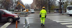 En arbetare i gula arbetskläder går över gatan vid övergångsstället vid Åbo Domkyrka, och en bil åker förbi utan att stanna för honom.