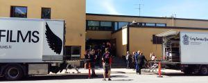 Lastbilar och människor väntar på en filminspelning vid T-talo i Åbo.