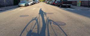 Skuggan av en cyklist över asfalten en tidig sommarmorgon i trähusstadsdelen Port Arthur i Åbo.