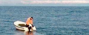 En kroatisk fiskare lägger ut nät från sin lilla båt.