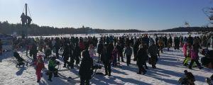 Mängder av människor står vid isen vid en sjö. Barn klättrar i en klätterställning till vänster i bild.