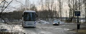 En lerig parkering där en buss och en personbil står parkerade. I bakgrunden skymtar stora högar med snö.