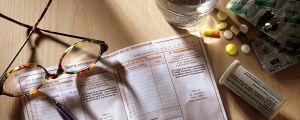 Glasögon, rexept, mediciner och vattenglad på ett bord.