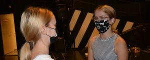 Ellen Kronberg, en flicka med svartvitrandig topp, glasögon och ett svartvitt Marimekkomunskydd står på en mörk teaterscen.