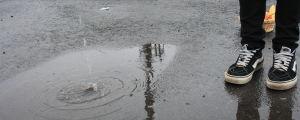 Fötter med ytterskor på vid en vattenpöl.