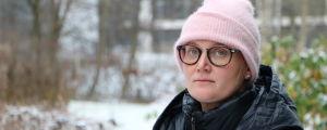 En kvinna i mössa och glasögon och vinterrock.