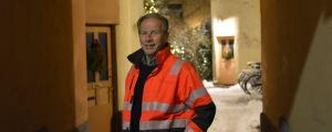Ben Mattsson i orange kläder står i en portgång med en julgran i bakgrunden.