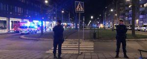 Polis står vid ett övergångsställe i Stockholm. I bakgrunden blinkande sirener och polisbilar.