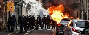 Bil som brinner på en gata, omgiven av poliser.