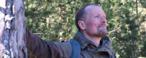 En medelålders man lutar med ena handen mot en stor tall. Han ler. I bakgrunden tallar. Mannen heter Esko Tainio, hän är naturvårdsexpert på Forststyrelsen.