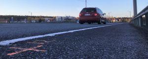 En T-korsning. En röd personbil som kör mot korsningen syns bakifrån. Det syns också trafikmärken, vägräcke och affärsbyggnader.