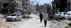En väg kantad med bombskadade byggnader i Douma i Syrien.
