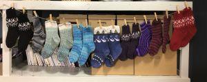 Många stickade sockor hänger på rad på en lina