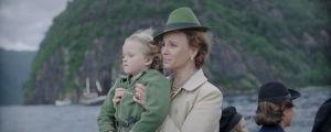 En liten trasnportbåt. Ombord ser vi Märtha som håller i sonen Harald och de tittar båda framåt.