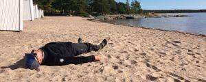 Mikko Peltola makaa Hangossa rantahiekalla.