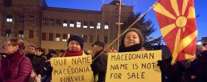 Två demonstrerande damer håller upp skyltar som visar att de är emot att Makedonien gör kompromisser med Grekland i namnkonflikten.