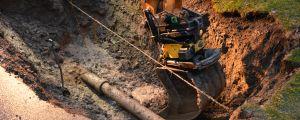 Vatten- eller avloppsrör i en grop, grävmaskinsskopan syns och det är vatten i gropen. Läckage.