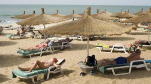 Människor ligger utsträckta i solen och i skuggan under parasoll på Senegambia beach i Gambia.