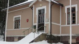 Ett gammalt stor trähus med myclet snö omkring.